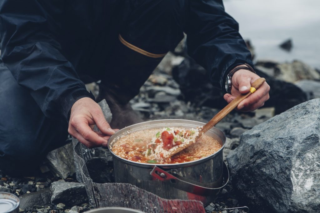 A wild camper stirring hot food in a pot cooking over a fire.
